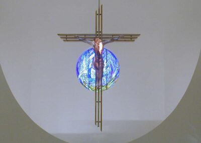 DIVINE SAVIOR Orangevale, California - The crystal corpus cast in clear resin hangs on a three beam maple cross. The maple, symbolic of the resurrection, and the three beams remind us of the Trinity. The crystal corpus leads us to the light of the world. The stained glass behind transmits the blues of the incarnation thru the corpus. Birth... Death... Resurrection.